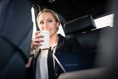 Geschäftsfrau, die Mitnehmerkaffee im Auto trinkt stockbild