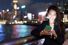 Geschäftsfrau, die an Mobiltelefon an im Freien arbeitet Stockfotografie