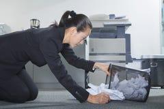 Geschäftsfrau, die nach Papieren in Trashcan sucht stockbild