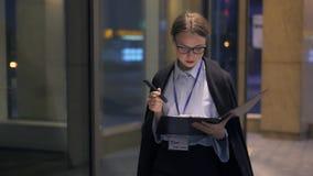 Geschäftsfrau, die in Nachtstadt geht und Dokument in ihrem Klemmbrett liest stock video footage