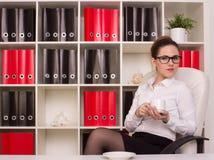 Geschäftsfrau, die nahe dem Schreibtisch sitzt Lizenzfreies Stockbild