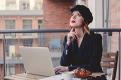 Geschäftsfrau, die nahe einer Tabelle in der Frühstückszeit sitzt Stockfotografie