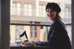 Geschäftsfrau, die nahe einer Tabelle in der Frühstückszeit sitzt Lizenzfreie Stockfotografie