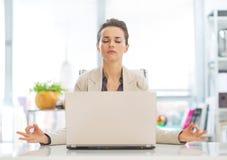 Geschäftsfrau, die nahe Laptop meditiert Stockfoto