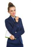 Geschäftsfrau, die Notizbuch hält und Stift auf dem Kinn, denkend stillsteht Stockbilder