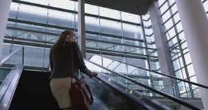 Geschäftsfrau, die oben auf Rolltreppe im Büro 4k umzieht stock video