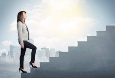Geschäftsfrau, die oben ein konkretes Treppenhauskonzept klettert Lizenzfreies Stockbild