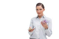 Geschäftsfrau, die Packs des Bargeldes hält und Kamera betrachtet Lizenzfreie Stockfotografie