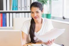 Geschäftsfrau, die Papiere am Schreibtisch hält stockbild
