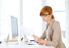 Geschäftsfrau, die Papiere untersucht Lizenzfreies Stockfoto