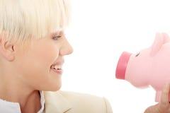Geschäftsfrau, die piggy Querneigung anhält Stockfotos