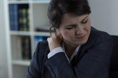 Geschäftsfrau, die Rückenschmerzen hat stockfoto