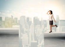 Geschäftsfrau, die am Rand der Dachspitze steht Lizenzfreies Stockbild