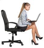 Geschäftsfrau, die am Rand des Bürostuhls sitzt Stockfotos