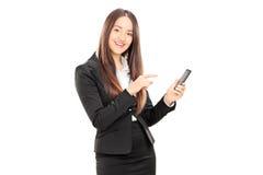 Geschäftsfrau, die in Richtung zu einem Handy zeigt Stockfotos