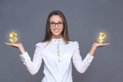 Geschäftsfrau, die Rubel und Dollarsymbole oder -zeichen hält Stockbild