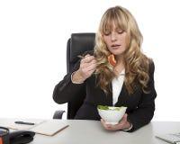 Geschäftsfrau, die Salat an ihrem Schreibtisch isst Stockfoto