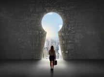 Geschäftsfrau, die Schlüsselloch mit hellem Stadtbildkonzept betrachtet lizenzfreie stockfotos