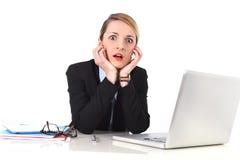 Geschäftsfrau, die am Schreibtisch arbeitet mit Laptop im Druck schaut umgekippt sitzt Stockfotos