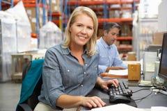 Geschäftsfrau, die am Schreibtisch im Lager arbeitet Lizenzfreie Stockfotos
