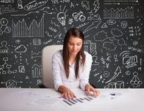Geschäftsfrau, die am Schreibtisch mit Geschäftsentwurf und -ikonen sitzt Lizenzfreie Stockbilder