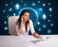 Geschäftsfrau, die am Schreibtisch mit Sozialnetzikonen sitzt Stockfotos