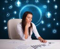 Geschäftsfrau, die am Schreibtisch mit Sozialnetzikonen sitzt Stockfoto