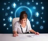 Geschäftsfrau, die am Schreibtisch mit Sozialnetzikonen sitzt Lizenzfreie Stockfotos