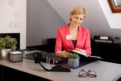 Geschäftsfrau, die am Schreibtisch sitzt Lizenzfreie Stockbilder