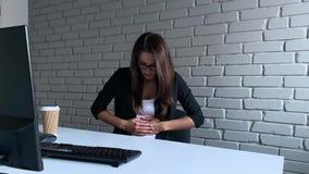 Geschäftsfrau, die am Schreibtisch sitzt und Magenschmerzen beim Arbeiten auf PC-Computer im Büro hat stock footage