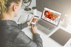 Geschäftsfrau, die am Schreibtisch sitzt und Smartphone und Laptop mit Grafiken, Diagramme, Daten, Diagramme auf Schirm verwendet stockfotografie