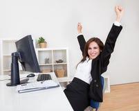 Geschäftsfrau, die am Schreibtisch zujubelt Lizenzfreie Stockbilder
