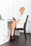 Geschäftsfrau, die sitzenden Schreibtisch der Tablette verwendet Lizenzfreie Stockfotos