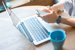 Geschäftsfrau, die Smartphone und Laptop verwendet stockbild