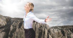 Geschäftsfrau, die Sonne gegen Felsen und bewölkten Himmel genießt Stockbilder