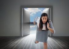 Geschäftsfrau, die in Tür von der Außenseite läuft Stockbild