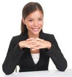 Geschäftsfrau, die am Tabellenlächeln sitzt Stockfotos