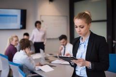 Geschäftsfrau, die an Tablette am Konferenzzimmer arbeitet Stockfotos