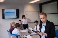 Geschäftsfrau, die an Tablette am Konferenzzimmer arbeitet Stockfotografie