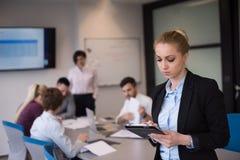 Geschäftsfrau, die an Tablette am Konferenzzimmer arbeitet Lizenzfreie Stockbilder