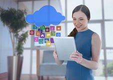 Geschäftsfrau, die Tablette mit apps Ikonen im Büro durch Fenster hält Stockfotografie