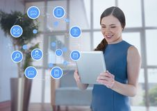 Geschäftsfrau, die Tablette mit apps Ikonen im Büro durch Fenster hält Lizenzfreie Stockfotografie