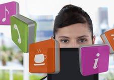 Geschäftsfrau, die Tablette mit apps Ikonen im hellen Büro hält Stockfotografie