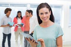 Geschäftsfrau, die Tablette verwendet und an der Kamera lächelt Stockfoto