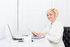 Geschäftsfrau, die Tablettenschreibtisch verwendet Stockfotos