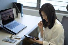 Geschäftsfrau, die Taschenrechner im Büro verwendet lizenzfreie stockbilder