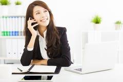 Geschäftsfrau, die am Telefon im Büro spricht stockbild