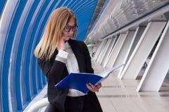 Geschäftsfrau, die am Telefon spricht und den Ordner mit Dokumenten betrachtet Stockfotos