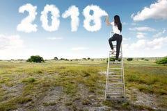 Geschäftsfrau, die Treppe verwendet und weiße Wolke mit 2018 SH spritzt Lizenzfreie Stockfotografie
