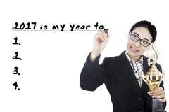 Geschäftsfrau, die Trophäe hält und eine Liste schreibt Stockfotografie